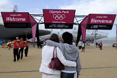Young couple - a white girl and an Asian boy - embrace as ticket holders around them enter the Olympic Park in Stratford on the first competitve day of the London2012 Olympic Games, with The Orbit to... - Stefano Cagnoni - 28-07-2012