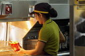 Catering staff dishing up chips at McDonalds inside the Olympic Park in Stratford, one of the major companies sponsoring the London2012 Olympic Games. McDonalds has restricted the market within the Ol... - Stefano Cagnoni - 26-07-2012