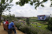 Sports fans in the Olympic Park in Stratford on the first competitve day of the London2012 Olympic Games watch televised events on big screens set up especially for the purpose. The Olmpic Stadium is... - Stefano Cagnoni - 28-07-2012