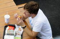 Man eating a McDonald's hamburger. - Stefano Cagnoni - 26-07-2012