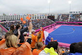 Dutch fans support their womens hockey team on an overcast day at the Riverside Arena in the Olympic Park in Stratford at the London 2012 Olympic Games. - Stefano Cagnoni - 2010s,2012,cheering,cities,city,crowd,crowds,Dutch,fan,fans,FEMALE,flag,flags,hockey,Leisure,LFL,LIFE,London,London 2012,London2012,Olympic,Olympics,orange,Park,patriotism,people,person,persons,PHYSIC