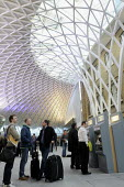 Commuters at the newly opened concourse with a latticework roof, King's Cross Station - Stefano Cagnoni - 2010s,2012,ACE,adult,adults,architecture,ARRIVAL,arrivals,arrive,arrived,arrives,arriving,automated,AUTOMATIC,AUTOMATION,bag,baggage,bags,buildings,busy,buy,buyer,buyers,buying,cities,city,commodities