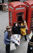 Tourists by iconic red telephone boxes in the West End of London - Stefano Cagnoni - ,2010s,2012,box,boxes,cities,city,communicating,communication,directions,EBF Economy,female,holiday,holiday maker,holiday makers,holidaymaker,holidaymakers,holidays,Leisure,LFL,LFL Leisure,LIFE,london