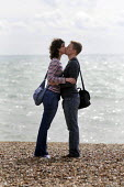 Couple kissing on the beach at Brighton. - Stefano Cagnoni - 2010s,2012,adult,adults,and,attraction,beach,beaches,boyfriend,BOYFRIENDS,COAST,coastal,coasts,couple,COUPLES,EMOTION,EMOTIONAL,EMOTIONS,FEMALE,girlfriend,girlfriends,happiness,happy,heterosexual,holi