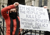 Funeral of Margaret Thatcher. Young woman wearing red, afraid to reveal her identity, stages a peaceful protest against Thatcherism and its damaging and divisive legacy, outside the High Court in the... - Stefano Cagnoni - 17-04-2013