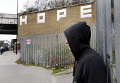 Young man on a street corner in north London with graffiti of the word: HOPE written on a wall beyond him. - Stefano Cagnoni - 2010s,2013,alone,benefit,benefits,bored,boredom,boring,cities,city,contemplating,contemplation,demoralised,demoralized,depressed,depression,deprivation,despair,despondent,disillusion,disillusioned,dis