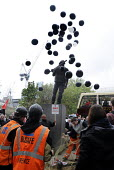 With the statue of the Building Worker above them, construction workers and apprentices release black balloons symbolising the lives lost in accidents in the construction industry in one year, Interna... - Stefano Cagnoni - 2010s,2014,accidents at work,activist,activists,against,balloon,balloons,Building,Building Worker,BUILDINGS,CAMPAIGN,campaigner,campaigners,CAMPAIGNING,CAMPAIGNS,capitalism,capitalist,Construction Wor