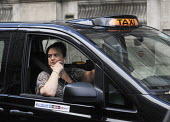 Woman taxi driver, and Arsenal Football Club supporter, at the steering wheel of her cab in Westminster, London. - Stefano Cagnoni - 24-09-2014