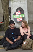 No to Austerity march, London, 2015. Couple relax at the end of their day's protest. - Stefano Cagnoni - 2010s,2015,activist,activists,adult,adults,against,anti,Austerity,Austerity Cuts,CAMPAIGN,campaigner,campaigners,CAMPAIGNING,CAMPAIGNS,Couple,COUPLES,cuts,DEMONSTRATING,demonstration,DEMONSTRATIONS,FE