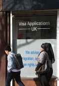 Woman and man passing offices advertising its legal advice for Visa Applications, immigration, asylum and human rights issues, Holloway, north London. - Stefano Cagnoni - 07-05-2015