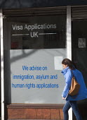 Woman passing offices advertising its legal advice for Visa Applications, immigration, asylum and human rights issues, Holloway, north London. - Stefano Cagnoni - 2010s,2015,advertising,advice,ADVISE,applications,asylum,Asylum Seeker,Asylum Seeker,cities,city,CLJ,Diaspora,displaced,female,foreign,foreigner,foreigners,help,HELPING,HELPS,Human Rights,IMMIGRANT,im