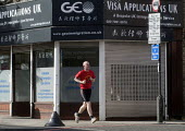 Male jogger passing offices advertising its legal advice for Visa Applications, immigration, asylum and human rights issues, Holloway, north London. - Stefano Cagnoni - 07-05-2015