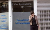 Woman talking on her mobile phone as she passes office advertising its legal advice for Visa Applications, immigration, asylum and human rights issues, Holloway, north London. - Stefano Cagnoni - 07-05-2015