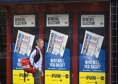 General Election, 2015. Postman passing by William Hill bookmakers shopfront advertising the betting odds on the General Election result, Holloway, north London. - Stefano Cagnoni - 2010s,2015,advertising,BET,bet betting,BETS,betting,betting shop,bookies,bookmakers,campaign,campaigning,CAMPAIGNS,DEMOCRACY,EBF Economy,Election,ELECTIONS,employee,employees,Employment,europeregi,gam