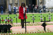 Young woman in red coat, carrying a red mobile phone, looks at the wooden crosses with poppies commemorating the dead of World War One, planted in the Royal Legion Field of Remembrance, Westminster, 2... - Stefano Cagnoni - 04-11-2015