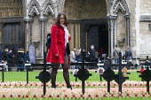 Young woman in red coat looks at the wooden crosses with poppies commemorating the dead of World War One, planted in the Royal Legion Field of Remembrance, Westminster, 2015. - Stefano Cagnoni - 04-11-2015