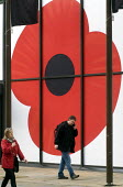 Man and woman walking along street, with large Poppy symbol on business premises behind them, London, 2015. - Stefano Cagnoni - 2010s,2015,ACE,business,cities,city,COLOR,colorful,colorfull,colors,colour,colourful,colours,COMMEMORATE,COMMEMORATING,commemoration,COMMEMORATIONS,Culture,FEMALE,London,memorial,people,person,persons