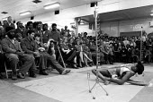 Limbo dancing in the canteen at the main Stamping and Body Plant, Ford Dagenham, Essex. The limbo was part of a lunchtime concert promoted by the GLC at the car plant - Stefano Cagnoni - 1980s,1982,ACE culture & entertainment,BAME,BAMEs,black,BME,bmes,BREAK,canteen,CANTEENS,car worker,car workers,cities,city,concert,CONCERTS,Council,culture,Dagenham,dance,dancer,dancers,dancing,DINNER