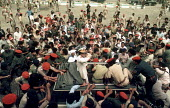 Colonel Gaddafi, leader of Libya, being mobbed by his subjects during celebrations in 1984 to mark the 15th anniversary of his coming to power. - Stefano Cagnoni - ,1980s,1984,african,anniversary,Arab,Arabic,Arabs,armed forces,army,CELEBRATE,celebrating,crowd,Gaddafi,head,leader,Libya,Libyan,Libyans,military,North Africans,of,people,pol politics Africa,security,