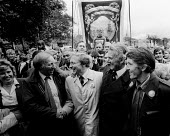 Durham Miners Gala NUM President Arthur Scargill greets Labour Party Leader Neil Kinnock to Kinnocks right are Peter Heathfield, NUM General Secretary, and Dennis Skinner MP. - Stefano Cagnoni - 1980s,1984,activist,activists,Arthur Scargill,banner,BANNERS,CAMPAIGN,campaigner,campaigners,CAMPAIGNING,CAMPAIGNS,County Durham,crowd,DEMONSTRATING,demonstration,DEMONSTRATIONS,disputes,INDUSTRIAL DI