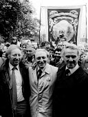 Durham Miners Gala NUM President Arthur Scargill greets Labour Party Leader Neil Kinnock to Kinnocks right is Peter Heathfield, NUM General Secretary - Stefano Cagnoni - 1980s,1984,activist,activists,Arthur Scargill,banner,BANNERS,CAMPAIGN,campaigner,campaigners,CAMPAIGNING,CAMPAIGNS,County Durham,crowd,DEMONSTRATING,demonstration,DEMONSTRATIONS,disputes,INDUSTRIAL DI