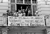 Striking miners children from the British coalfields give the victory sign on arrival in Lens as part of a group of children provided with a holiday in France as a gesture of solidarity by French trad... - Stefano Cagnoni - 1980s,1984,aid,assistance,badge,BADGES,balcony,banner,BANNERS,child,CHILDHOOD,children,coal industry,coalindustry,communicating,communication,DISPUTE,DISPUTES,EMOTION,EMOTIONAL,EMOTIONS,Europe,France,
