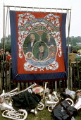 The Chopwell Lodge banner of the NUM, Durham Miners Gala, 1986. The Red Banner is famous as it contains images of Karl Marx, Vladimir Lenin and Keir Hardie - Stefano Cagnoni - 1980s,1986,band bands,banner,banners,brass,brass band,brass bands,brass instrument,brass instruments,communism,communist party,communists,County Durham,disputes,Durham Miners Gala,INDUSTRIAL DISPUTE,K