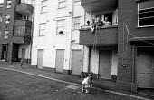 Children playing on an improvised swing, watched by their family, on a council housing estate in a poor area of Plymouth - Stefano Cagnoni - 02-09-1991
