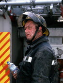 Firefighter resting after helping his colleagues to extinguish a house fire - Stefano Cagnoni - 1990s,1998,adult,adults,bottle,bottled,bottles,cities,city,dehydrated,dehydration,DIA disasters & accidents,dirt,drink,Emergency Services,employee,employees,Employment,EXHAUSTED,EXHAUSTION,fire,fire a