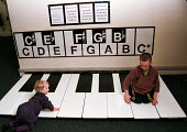 Able bodied chilld playing alongside disabled child on the walk-on keyboard at the Stradivarium, an area of the Exploratory Science Museum in Bristol devoted to sound and music - Stefano Cagnoni - 27-02-1999