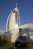 A 4x4 SUV for sale at an advertising feature for a dealership with the Burj Al Arab luxury Hotel behind, Dubai, UAE. - Simon Edwards - 06-10-2007