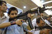 An Iranian boy shoots at target with a laser gun, during a police exhabition in Tehran ,Iran. - Siavash Habibollahi - 25-06-2008