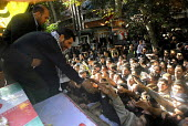 Iran's president Mahmoud Ahmadinejad waves to people near the coffins during of a funeral ceremony was held to commemorate the deaths of the unidentified soldiers, in Tehran, Iran.  Recently recovere... - Siavash Habibollahi - 06-11-2007