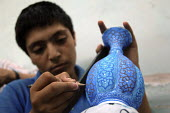 An Iranian boy decorates a vase in a workshop in Isfahan, 450 km (280 miles) south of Tehran, Iran. June 17, 2008. - Siavash Habibollahi - 17-06-2008