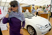 A wealthy Iranian woman speaks on her mobile front of a Mercedes Benz during a FEI world jumping challenge at the Norooz Abad Riding complex in Tehran, Iran. - Siavash Habibollahi - 07-09-2007
