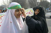 Iranian woman ties a islamic headband to a schoolgirl during a silent demonstration in Tehran, Iran to promote adherence to Iran's Islamic dress rules. Feb 8, 2008. - Siavash Habibollahi - 2000s,2008,activist,activists,adolescence,adolescent,adolescents,adult,adults,against,age,ageing population,CAMPAIGN,campaigner,campaigners,CAMPAIGNING,CAMPAIGNS,child,CHILDHOOD,children,code,daughter