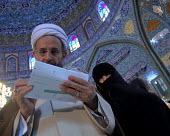 An Iranian clergyman with his wife casting votes in Iran's parliamentary election at polling station at the Hossineyeh Ershad mosque in Tehran, Iran. - Siavash Habibollahi - 14-03-2008