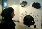 A woman looks to a poster at a conceptual art exhibition about HIV/AIDS in Tehran, Iran. - Siavash Habibollahi - 2000s,2007,ace art culture,Acquired immune,aids,artwork,artworks,deficiency syndrome,DISEASE,DISEASES,dress,exhibition,FEMALE,hajib,headscarf,HEALTH,hijab,hiv,immunodeficiency,infected,people,person,p