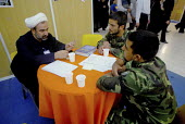 An Iranian clergyman speaks with two soldiers during the International Koran exhibition at the Imam Khomeini grand mosque in Tehran, Iran. Oct 4 , 2007. - Siavash Habibollahi - 02-10-2007