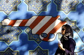 An Iranian woman passes in front of an Anti-American mural during a demonstration to commemorate Student Day in front of the old U.S Embassy in Tehran Iran . Militant students stormed in the embassy o... - Siavash Habibollahi - 04-11-2006