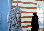 An Iranian woman passes in front of an Anti-American mural. - Siavash Habibollahi - ,2000s,2006,activist,activists,anti american,CAMPAIGN,campaigner,campaigners,CAMPAIGNING,CAMPAIGNS,death,DEATHS,DEMONSTRATING,demonstration,DEMONSTRATIONS,died,dress,FEMALE,flag,flags,hajib,headscarf,