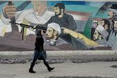 A woman walks past a mural painted on the wall in north of Tehran, Iran. - Siavash Habibollahi - 23-01-2008