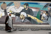 An Iranian clergyman walks past a war painted on the wall in north of Tehran, Iran. - Siavash Habibollahi - 23-01-2008