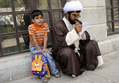 An Iranian clergyman reads a letter at the Faizieh school with his child in Qom city, Iran. - Siavash Habibollahi - 31-05-2007
