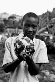 Burundi refugee child holds a home-made football made from plastic bags, Butare, Rwanda 2003 - Steven Langdon - 03-08-2003
