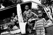 Three young Rwandan children play in an abandoned vehicle in Kigali. Rwanda, 2003 - Steven Langdon - 03-08-2003