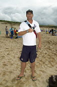 PCSO Paul Price patrolling Fistral Beach in Newquay Cornwall, in the Beach Beat scheme the Police Community Support Officers are also RNLI Lifeguards - Sam Morgan Moore - 2000s,2007,adult,adults,Beach,BEACHES,CLJ,COAST,coastal,coasts,communities,Community,community policing,crime,force,holiday,holiday maker,holiday makers,holidaymaker,holidaymakers,holidays,Lifeguard,L