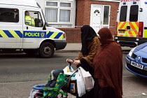 Police anti-terrorist raids in Sparkbrook Birmingham Local residents pass Police in Sparkhill after raids to foil an alledged terrorist plot. Birmingham. - Stalingrad O'Neill - 01-02-2007