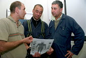 Asian building workers and a Lecturer in Trade Union Studies (far left) discuss industrial injuries with the help of a 'bodymapping' chart during a course on Health and Safety held on a construction s... - Janina Struk - 19-03-2004