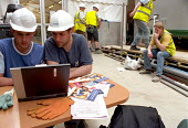 Building workers in hard hats on a construction site at Canary Wharf are introduced to basic computer skills on a laptop by a tutor from the nearby Learning Centre run by TUC, UCATT and Lewisham Colle... - Janina Struk - 25-05-2004